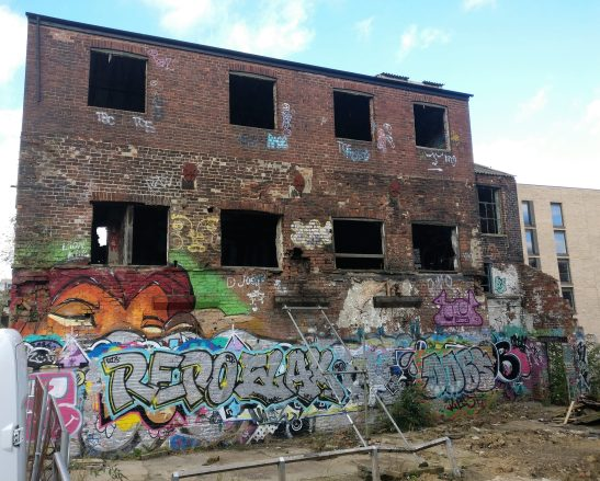 An abandoned building full of graffiti in the middle of the Sylvester Street car park