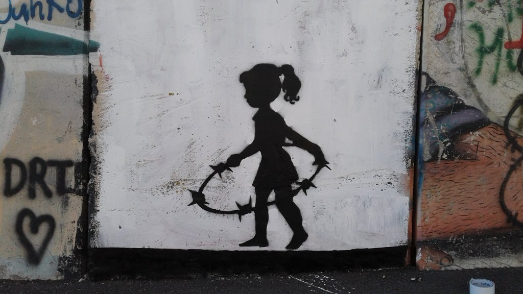 A girl plays with a barbed wire hula hoop by Cakes Stencils the artist