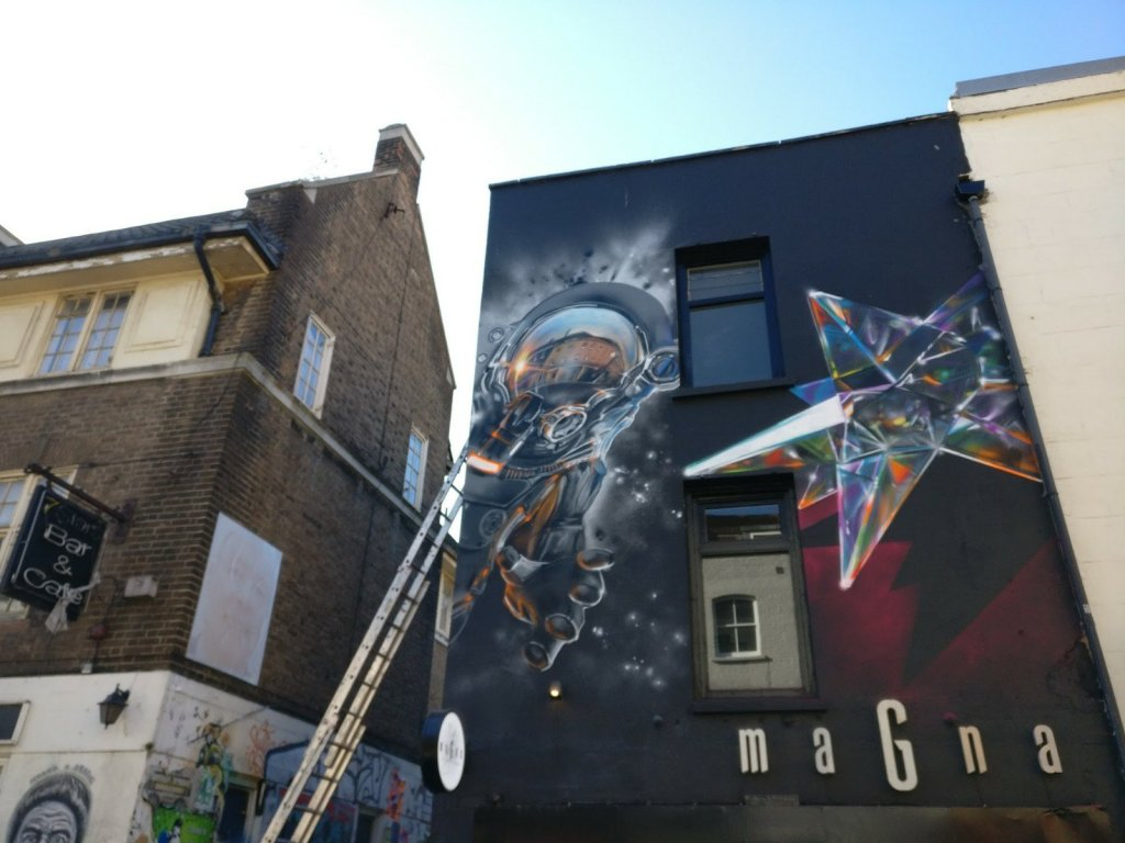 Mural of an Astronaut by Fanakapan on Brick Lane above Magna Donuts