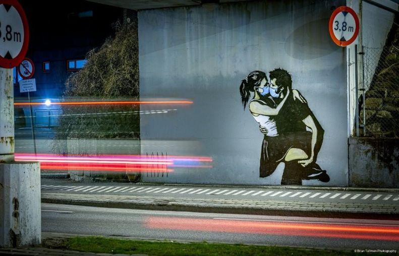 Lovers kissing with facemasks. Coronavirus street art in Norway