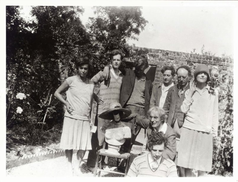 A photo of Francis Partridge, Quentin Bell, Julian Bell, Duncan Grant, Clive Bell, Beatrice Mayor, Roger Fry and Raymond Mortimer. They are in the garden of Charleston Farmhouse