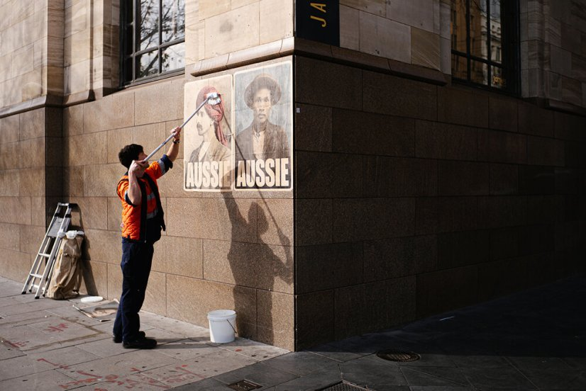 Artist Peter Drew pasting up his Aussie posters