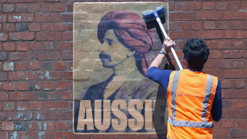 Artist Peter Drew pasting up an Aussie poster of Monga Khan