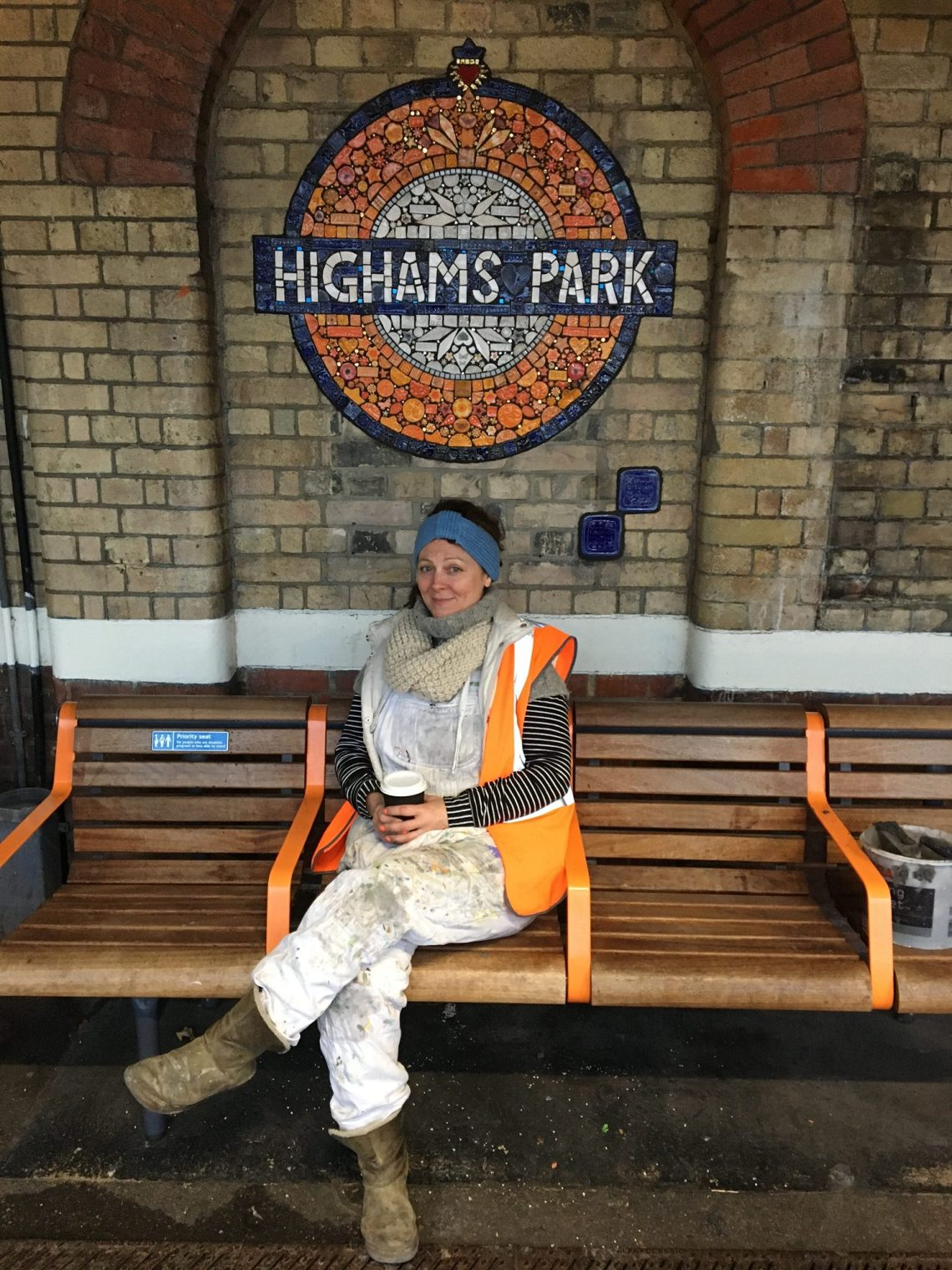 Maud Milton sits underneath the mosaic roundel at Highams Park station