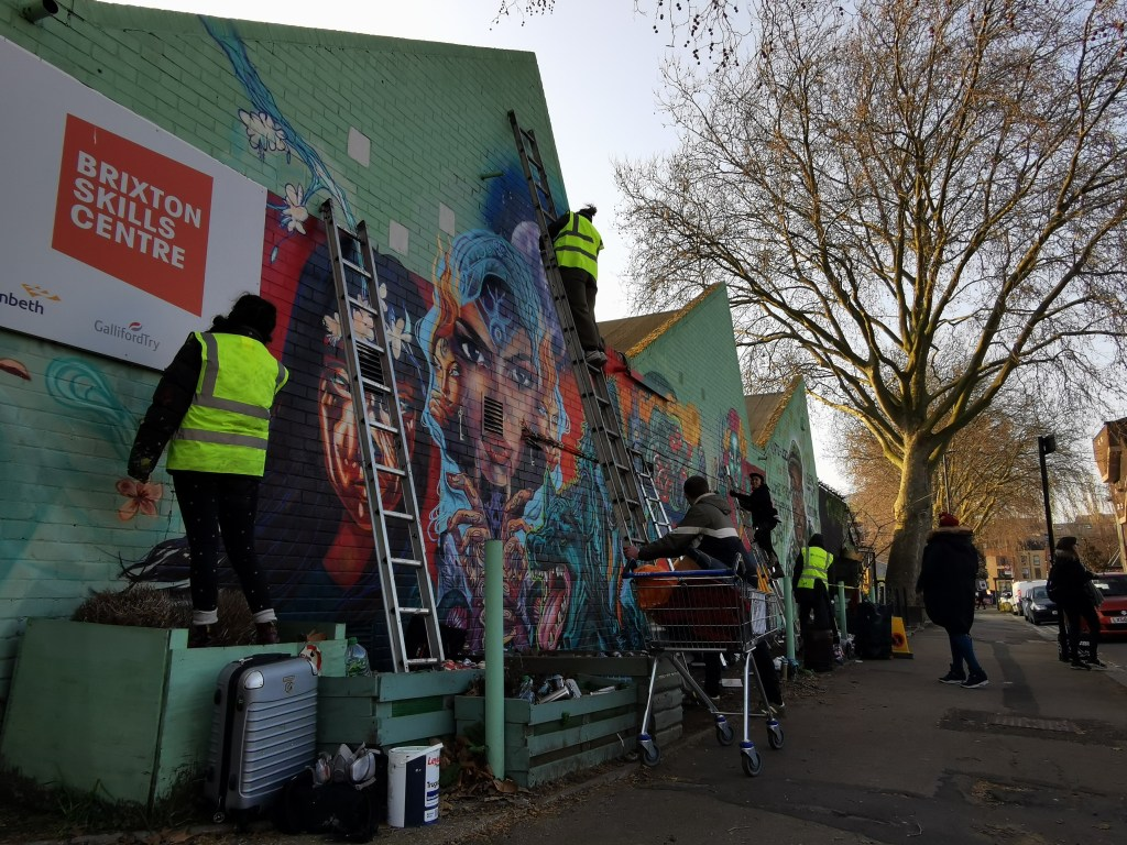 Female street artists painting in Brixton