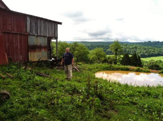 Photo of Eric Price and the c. 1905 barn on the farm where he grew up.