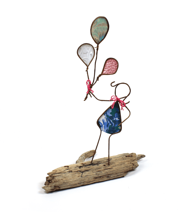 Image of Girl with Balloons, a sculpture in wire and cut paper on driftwood.