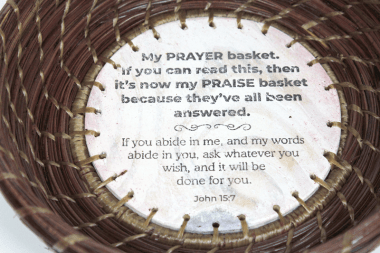Detail Image of a hand-woven pine straw basket by Patti Jones featuring a hand-made base with writing by Stephen Rountree and a Scripture from John 15:7