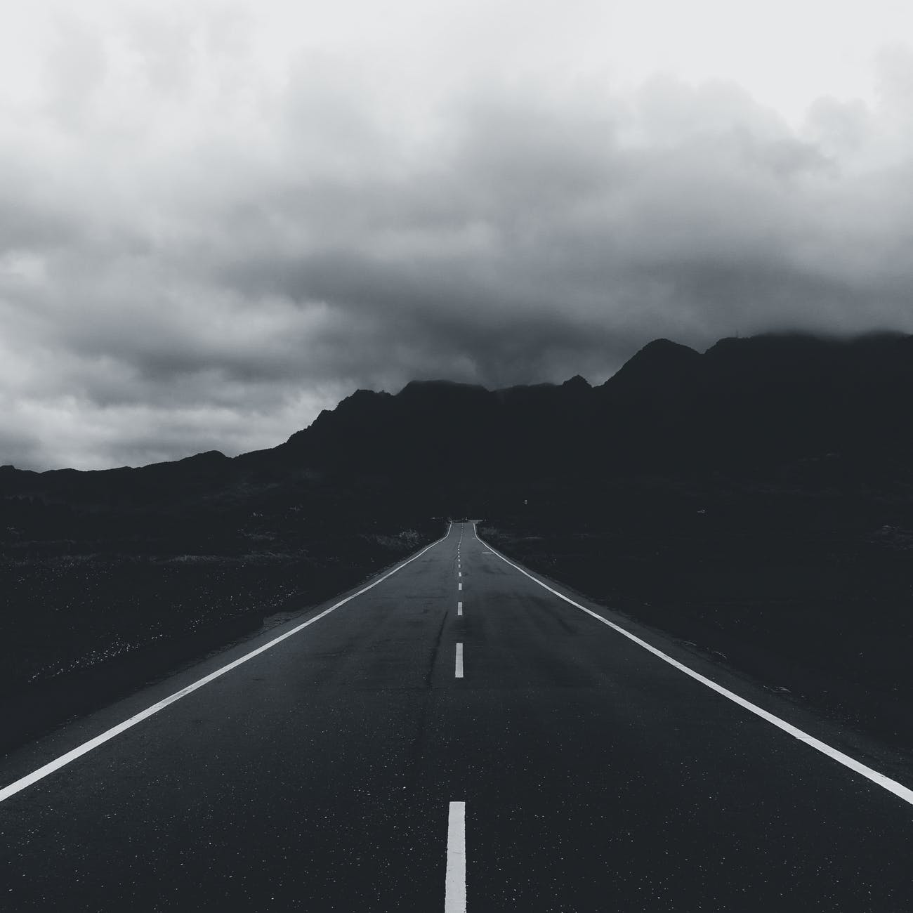 grayscale photo of a road heading to mountain