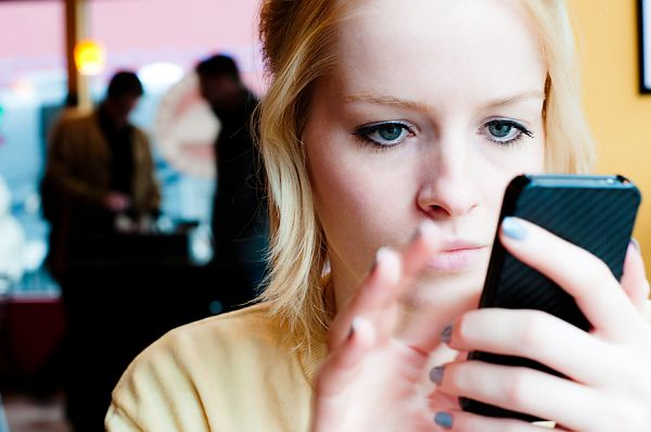 Image: A young woman uses a smart phone