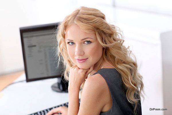 Back view of blonde woman working in office