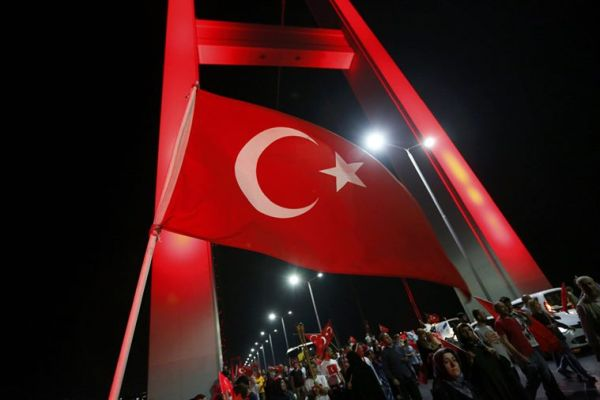 A Turkish national flag waves as pro-government demonstrators march over the Bosphorus Bridge, from the Asian to the European side of Istanbul, Turkey, July 21, 2016. REUTERS/Murad Sezer