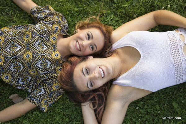 Shot from above, two happy girls having fun time, smiling.