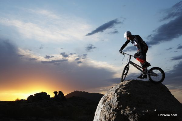Bike rider balancing on rock boulder, side view