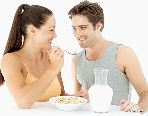 Young woman feeding a young man breakfast cereal