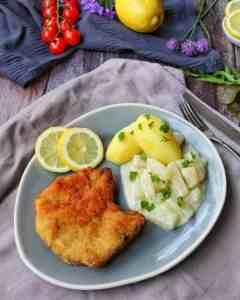 Panierte Koteletts mit Kohlrabi in heller Soße und Kartoffeln