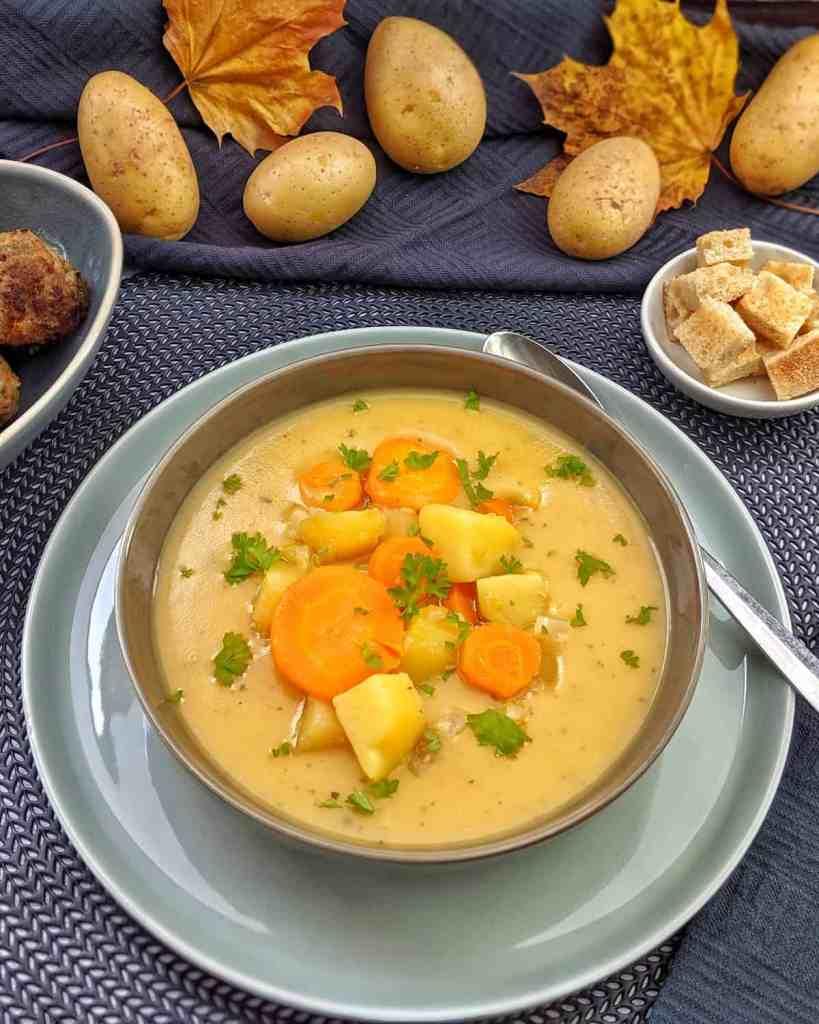 Kartoffelsuppe mit Hackbällchen. Im Hintergrund Deko.