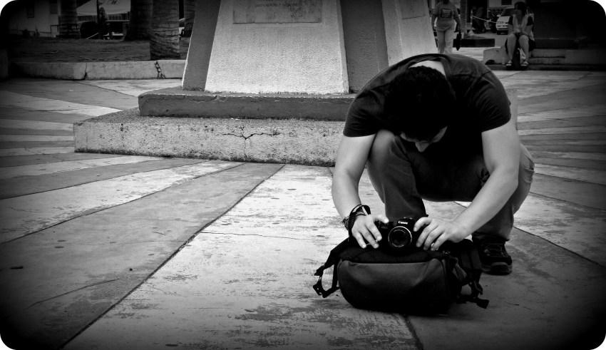 Foto en blanco y negro de Charles posicionando su cámara en nuestro bolso para tomar la foto de grupo