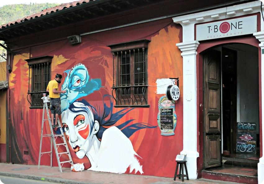 Graffeur en train de peindre sur un mur d'un restaurant de Bogotá