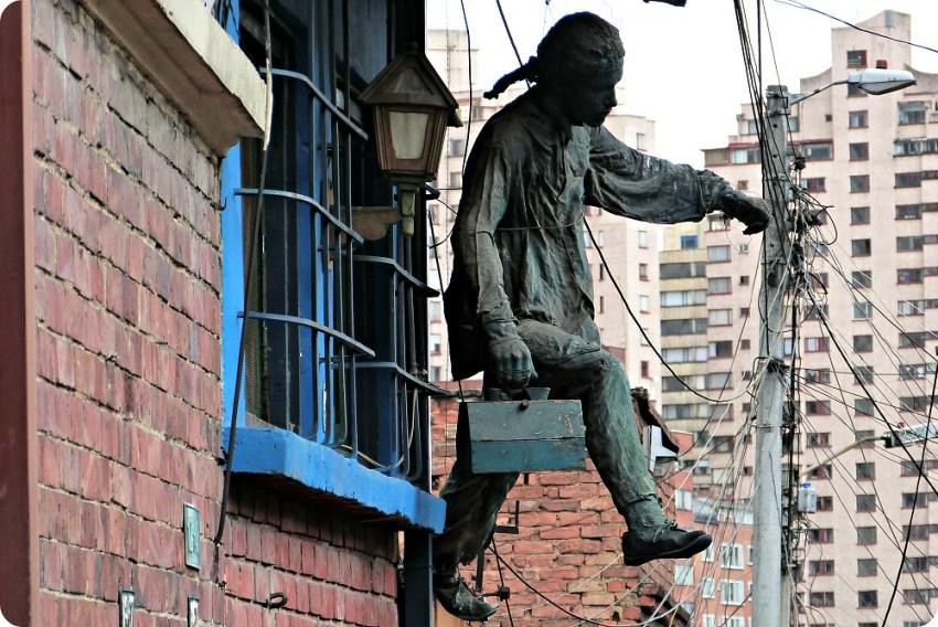 Escultura de un hombre llevando una maleta colgado a una ventana del barrio de la Candelaria en Bogotá