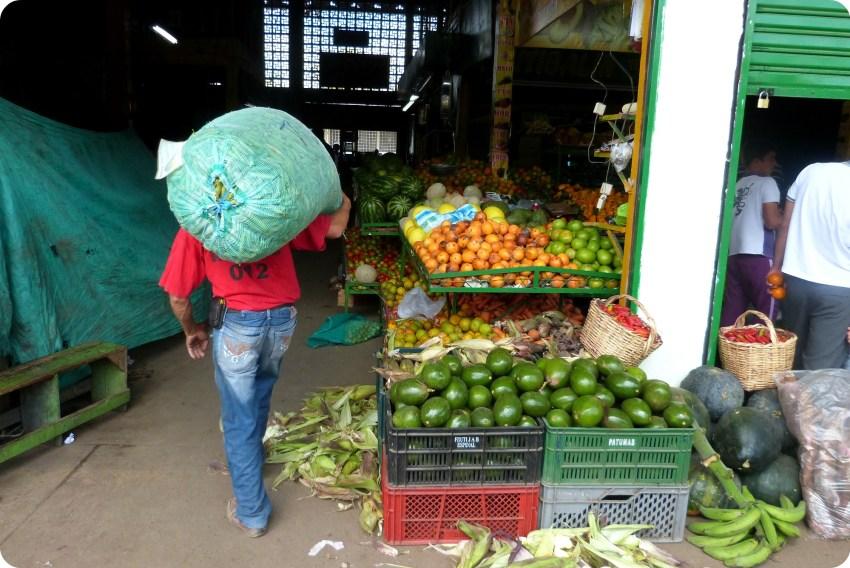 descargador con un bulto en el hombro en el mercado de Armenia