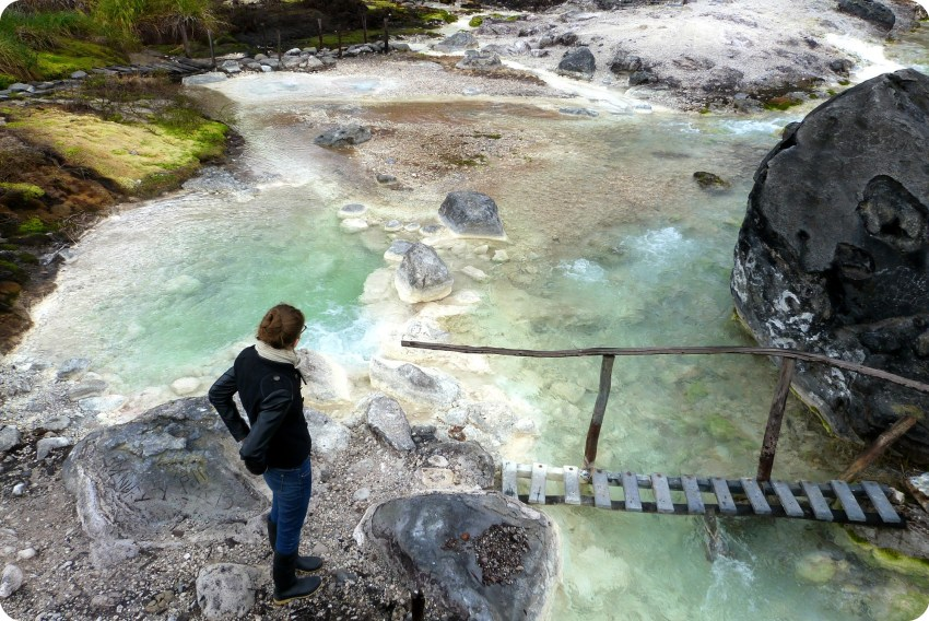 Charlène delante de un pequeño puente de madera sobre un curso de agua en los termales de san juan en el parque natural Puracé
