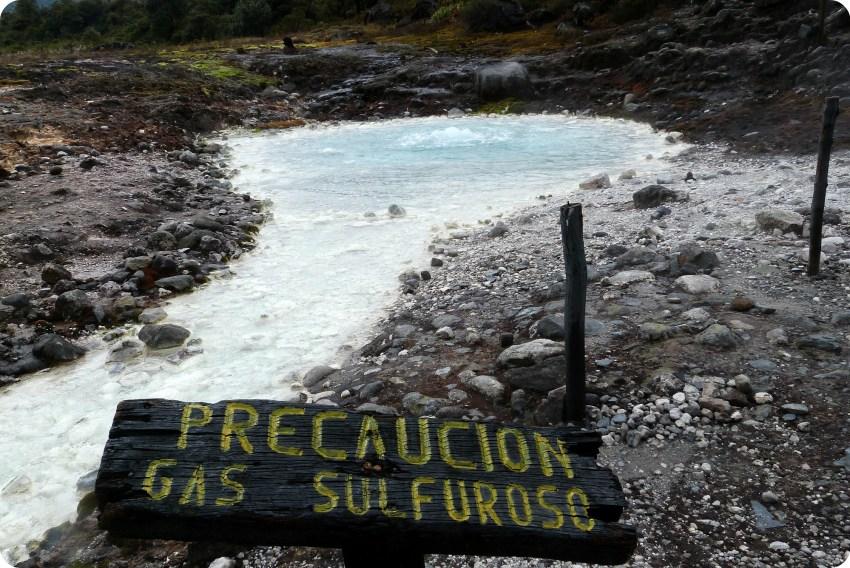 """piscina de agua termal con un cartel """"precaución gas sulfuroso"""" en los termales de san juan en el parque natural Puracé"""