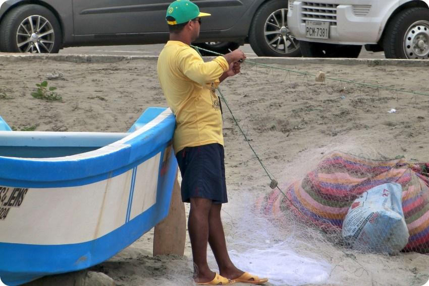 pêcheur rangeant son filet de pêche sur la plage de Pedernales