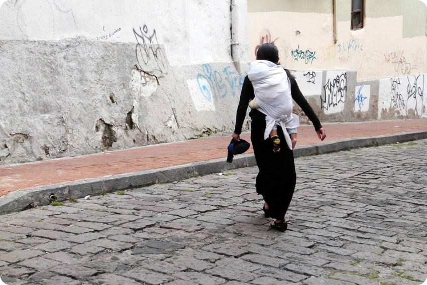 mujer ecuatoriana cruzando una calle de Quito cargando un bebé en la espalda