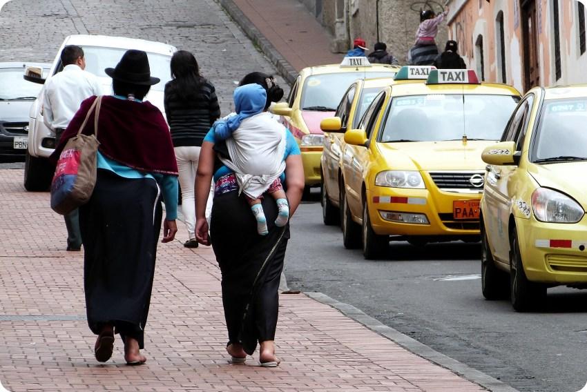 mujeres ecuatorianas en un andén de Quito y una cargando un bebé en la espalda