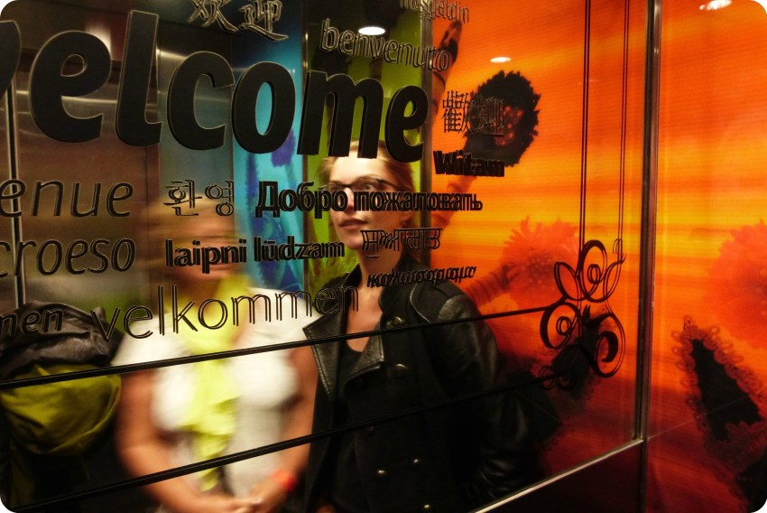 """Palabra """"bienvenida"""" escrita en varios idiomas en el espejo del ascensor del museo de la Mitad del Mundo de Quito"""