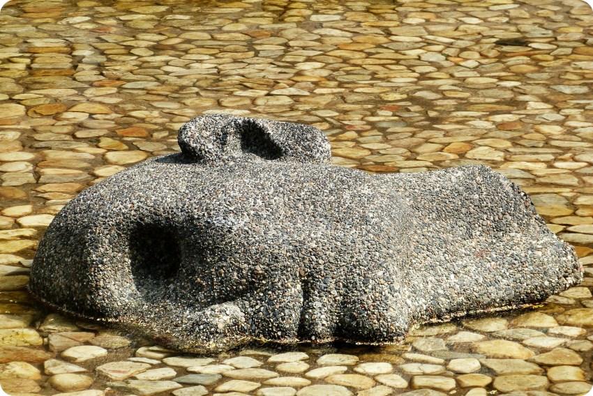 détail d'une moitié de visage dans l'eau de la sculpture Fuente de la vida de Medellín