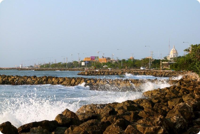 Pequeñas olas que se rompen en las rocas con un edificio del centro de la ciudad de Cartagena en el fondo de la foto