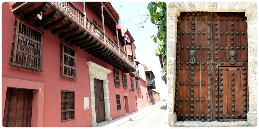 Maison rouge avec une porte en bois très imposante remplie d'énormes clous et de deux heurtoirs pour frapper dans une rue de Carthagène
