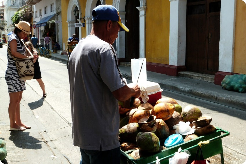 hombre cortando un coco fresco sobre su carrito en una calle de Cartagena