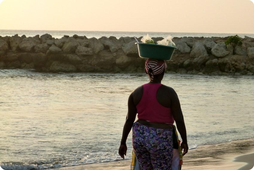 una mujer transporta sobre su cabeza la comida que vende a los turistas en una playa de Cartagena