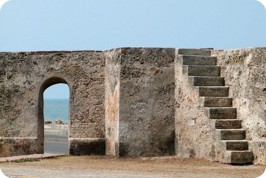 """escalier menant sur les murailles de la ville de Carthagène et vue de la mer des Caraïbes à travers une """"porte"""" taillée dans la pierre"""