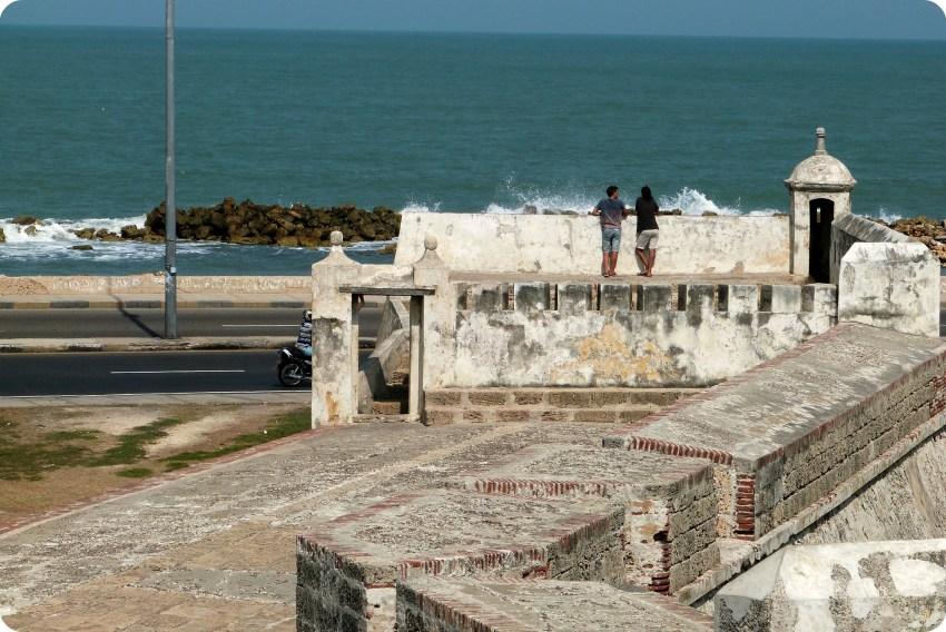 2 hombres de espalda de dos apoyándose en los codos sobre las murallas de Cartagena hablando y mirando el mar Caribe en el fondo