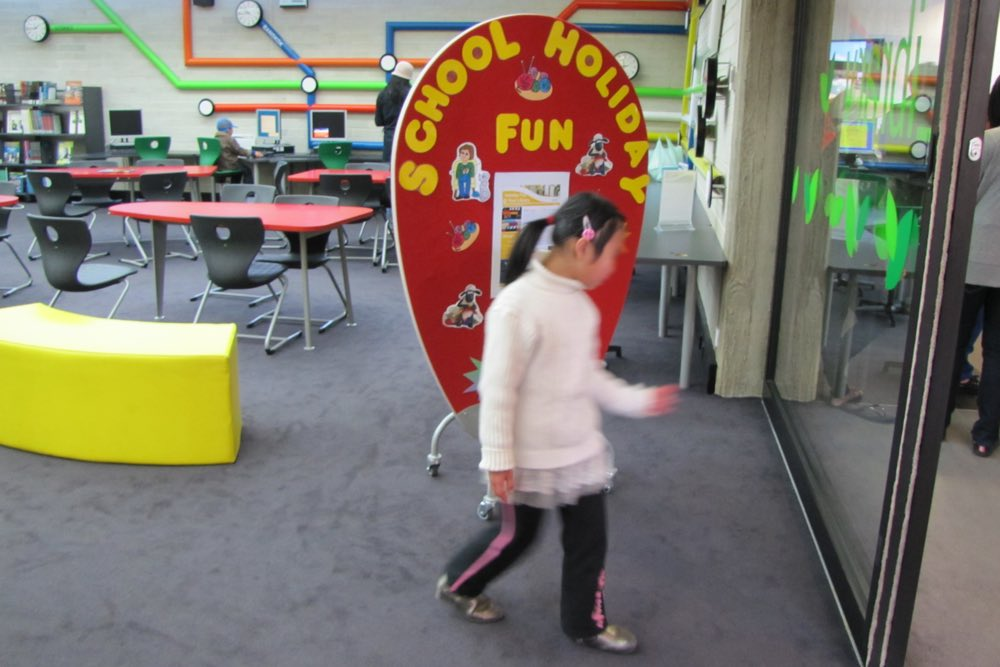 EGG Screen displays school holiday fun, at the entrance to Whitlam Library.