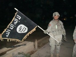 U.S._Army_soldier_with_captured_ISIS_flag_in_Iraq,_December_2010.jpg