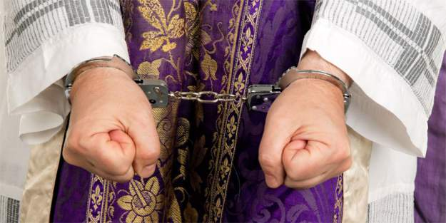 Stock photo of Catholic priest in handcuffs