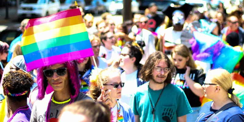 A rainbow flag held above the heads of young people in a crowd