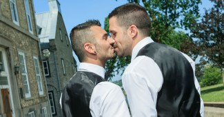 A gay couple kisses after their wedding