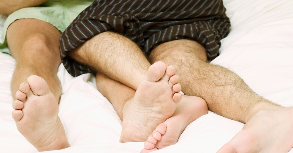 Two mens' legs intertwined on a bed