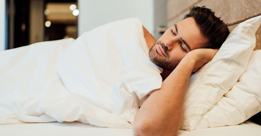 A man sleeps with his hands handy