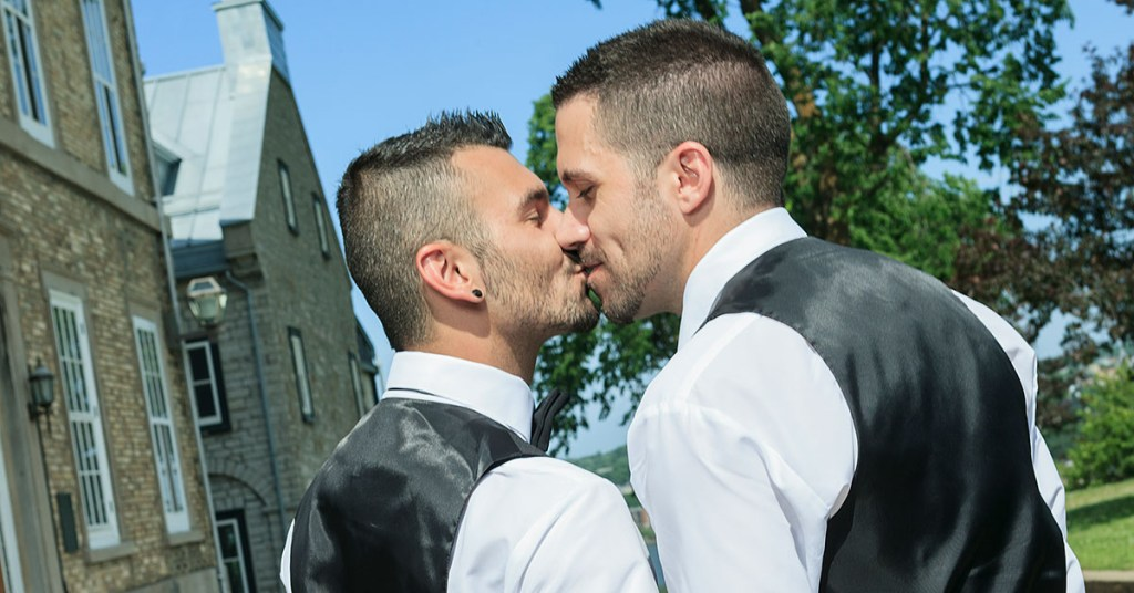 Two men kissing after saying wedding vows