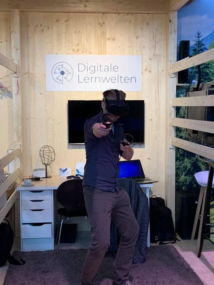 Ein Mitarbeiter des Instituts für digtales Lernen bedient auf der Fankfurter Buchmesse eine VR-Brille