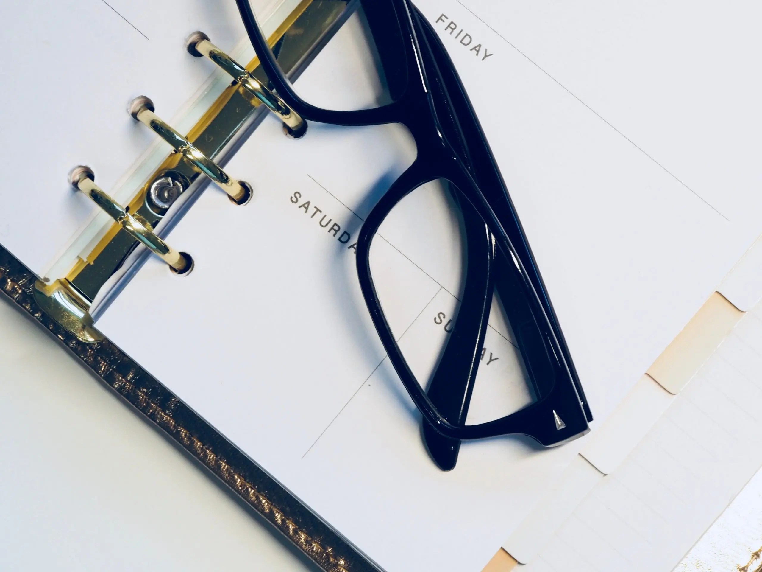 Planner with eyeglasses resting on top