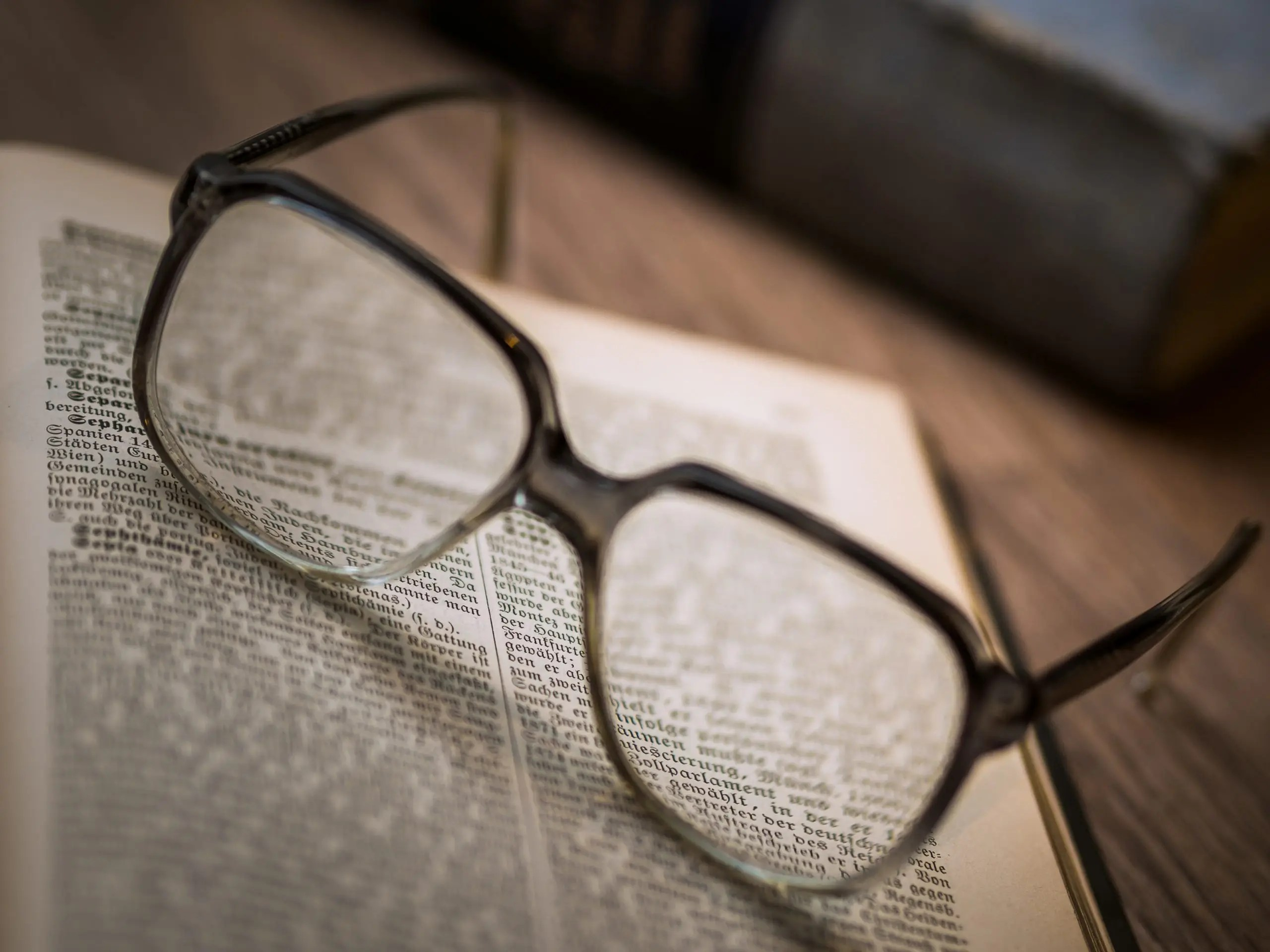 Image of eyeglasses resting on an open book