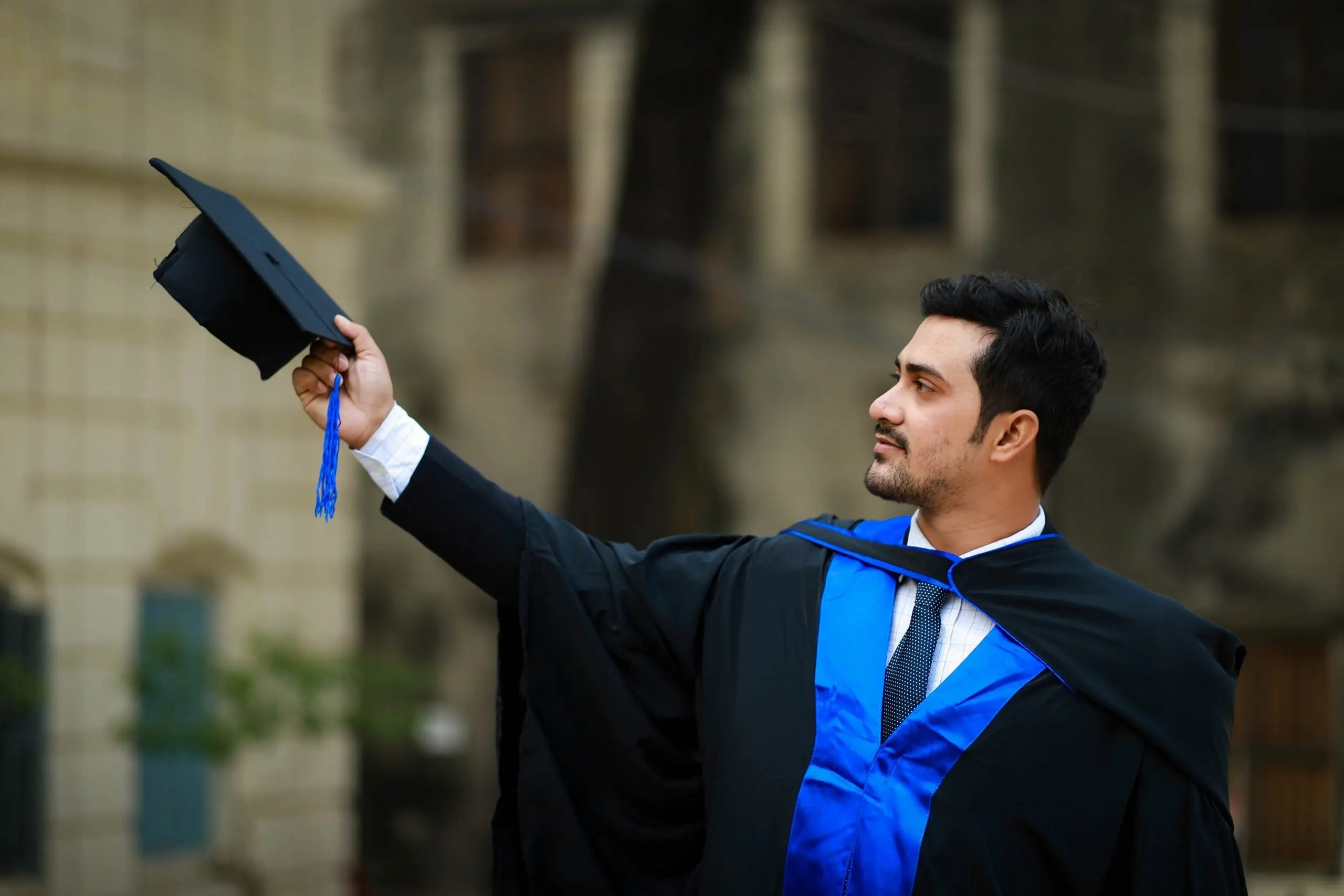 Male graduate in a cap and gown - symbolizing student success